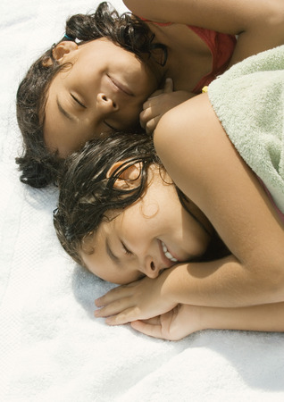 Two girls lying down together, one wrapped in towel