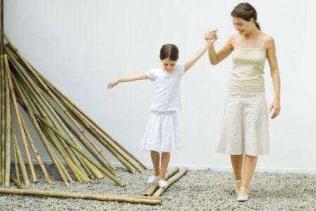 Girl balancing on bamboo, mother helping her by holding her hand LANG_EVOIMAGES