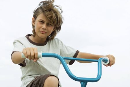 Boy on bicycle, looking at camera, portrait