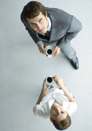 Business associates holding cups of coffee, looking up at camera, full length, high angle view LANG_EVOIMAGES