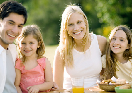 Family sitting at table outdoors, smiling LANG_EVOIMAGES