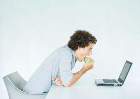 Young man sitting at table, eating apple and using laptop LANG_EVOIMAGES