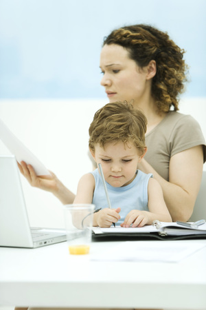 distractions: Mother holding son on lap, sitting in front of laptop, frowning at document LANG_EVOIMAGES