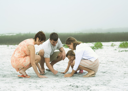 Family playing in sand together LANG_EVOIMAGES