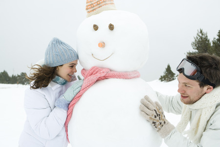 Two young friends peeking around snowman at each other, smiling