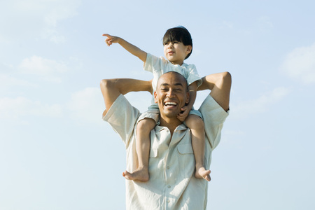 Father carrying son on shoulders and smiling at camera, child pointing and looking away LANG_EVOIMAGES