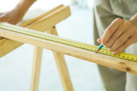 Unrecognizable person measuring wood with measuring tape