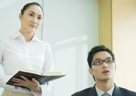 Business executive and woman holding agenda, both looking out of frame