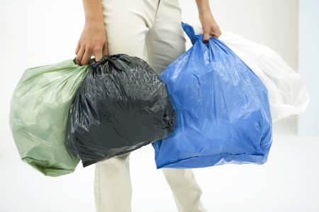 Female carrying several bags of garbage, cropped view