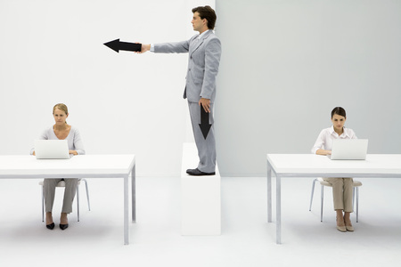 authoritative woman: Professional women working in office, man standing between them, pointing arrow