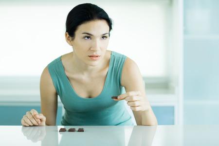 Woman eating chunks of chocolate, looking away