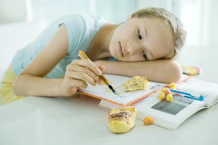 Dívka sedící u stolu dělá domácí úkoly, odpočívá hlavu na paží, doodling, jídlo rozptýlené na knihy LANG_EVOIMAGES