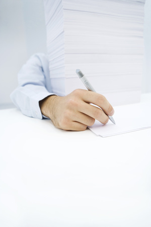 burned out: Arm reaching around massive stack of paper to write on a single sheet