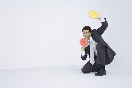 Businessman holding up two clocks LANG_EVOIMAGES