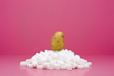 Food concept, potato on top of pile of sugar cubes