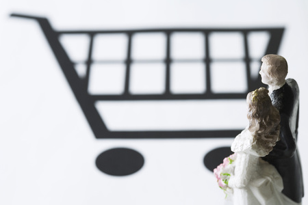 Bride and groom figures looking at shopping cart