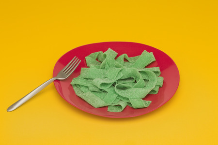 Food concept, plate of green gummy candy arranged like pasta