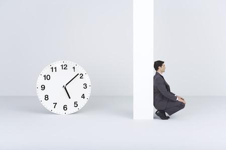 Businessman waiting, near oversized clock