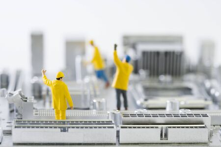 Miniature technicians standing on computer motherboard with arms raised LANG_EVOIMAGES
