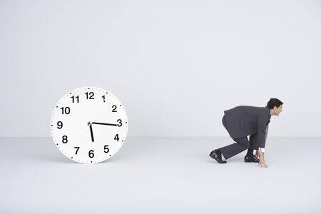 Businessman crouching, ready to run, next to clock