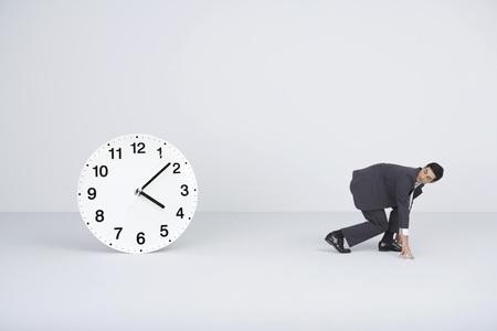 Businessman racing against time, looking over shoulder at large clock LANG_EVOIMAGES