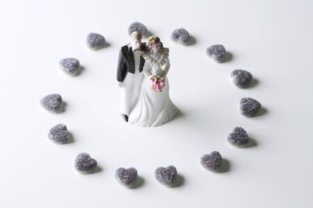 Miniature bride and groom surrounded by candy hearts