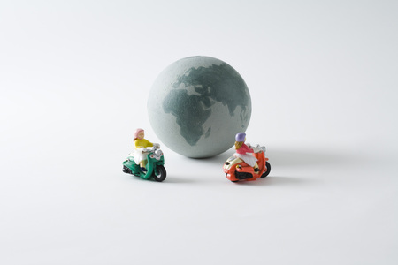 Miniature mopeds riding around globe LANG_EVOIMAGES