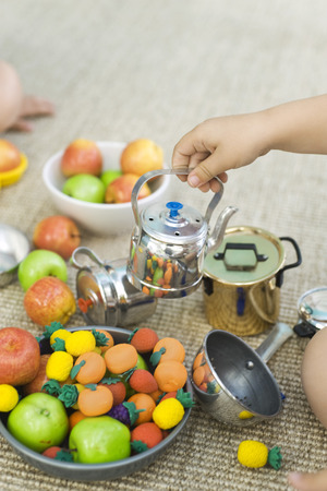Children playing with teapot and fake food, cropped view LANG_EVOIMAGES