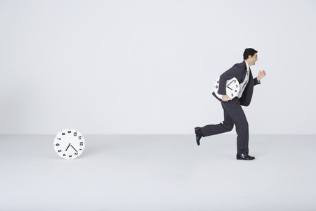Businessman running with clock, leaving second clock behind LANG_EVOIMAGES