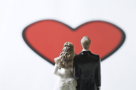 heartshaped: Miniature bride and groom standing in front of large heart graphic