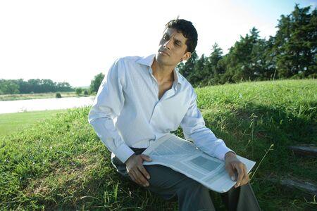Businessman sitting on grass, holding newspaper