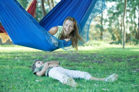 Mother and boy, woman lying in hammock while boy lies on grass