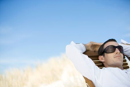 Young man sitting in deck chair, wearing sunglasses