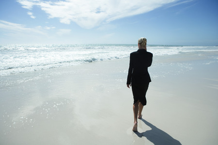 Businesswoman using cell phone, walking barefoot across beach, full length, rear view