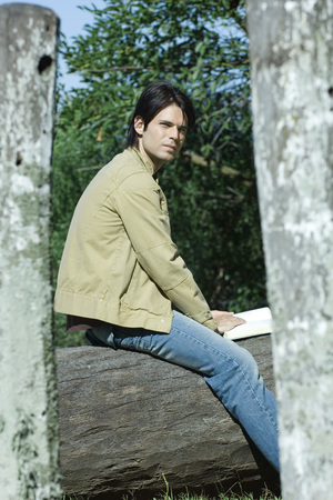 Man sitting on tree trunk with book, looking away