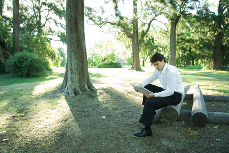 Businessman sitting on logs, reading newspaper