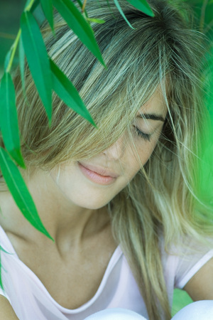 Young woman among foliage, hair covering face, eyes closed LANG_EVOIMAGES