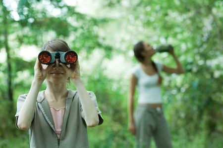 getting out: Woman looking through binoculars while friend drinks water in background
