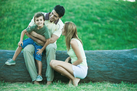Boy with parents, sitting on fathers lap LANG_EVOIMAGES