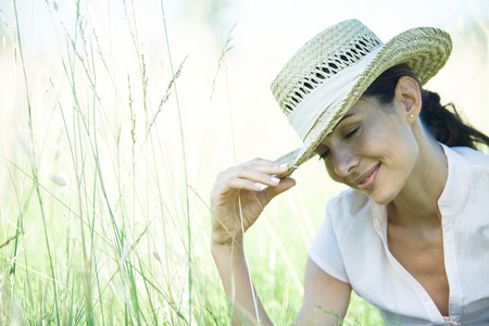 Woman in field, holding edge of hat LANG_EVOIMAGES
