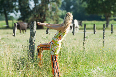 chainlink fence: Young woman holding on to rural fence, side view
