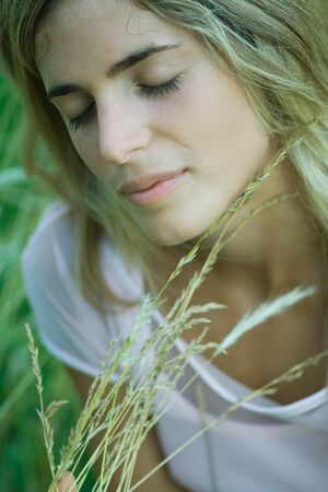 Young woman holding tall grass, eyes closed, close-up LANG_EVOIMAGES