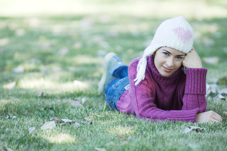Young woman lying on grass, wearing knit hat and sweater
