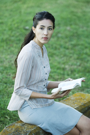 Woman sitting outdoors, reading book, looking up at camera