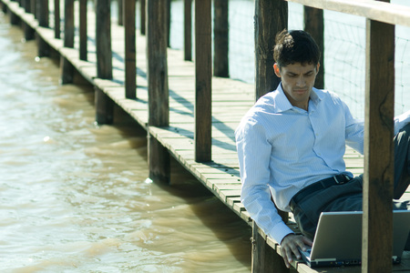 Businessman on wooden footbridge over lake, using laptop