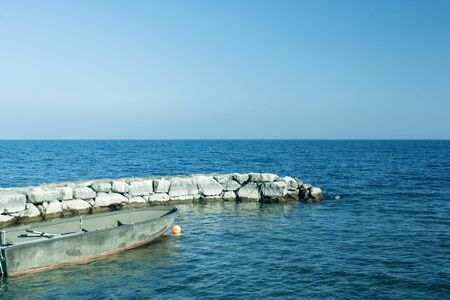 seascapes: Rowboat and breakwater in lake