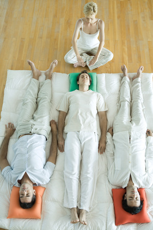 esoterismo: Alternative therapy session, three adults lying side by side while therapist puts hands out over mans head
