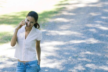 Casually dressed woman using cell phone, smiling as she walks through park