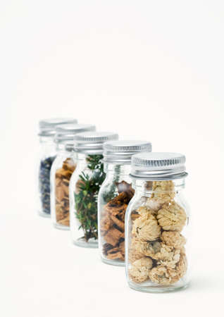 Bottles containing dried flowers, herbs, and wood shavings