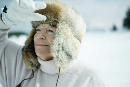 furs: Senior woman standing in snowy landscape, shading eyes, head and shoulders